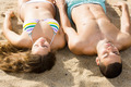 Handsome guy and his girlfriend laying on sand - PhotoDune Item for Sale