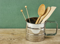 wooden kitchenware in metal jug  on old wooden table over green - PhotoDune Item for Sale