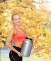 smiling sporty woman with jar of protein - PhotoDune Item for Sale