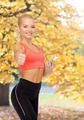 smiling sporty woman with smartphone - PhotoDune Item for Sale
