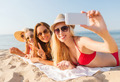 group of smiling women with smartphone on beach - PhotoDune Item for Sale