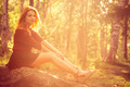 Young Woman relaxing outdoor in sunny forest alone Lifestyle