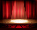 A theater stage with a red curtain, seats and a spotlight - PhotoDune Item for Sale