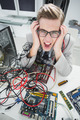 Stressed computer engineer working on broken cables in his office