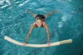 Fit blonde swimming with foam roller in swimming pool at the leisure centre