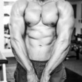 Close up mid section of a shirtless muscular man flexing muscles in gym