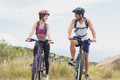 Low angle view of an athletic couple mountain biking