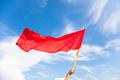 Hand waving a red flag with blue sky background in outdoors - PhotoDune Item for Sale