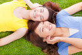 two asian pretty young woman lying on grassland and listening music - PhotoDune Item for Sale