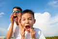 father and son making a grimace together in the park with blue sky background - PhotoDune Item for Sale