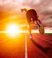 Athletic young man running on race track with sunset background.sport concept - PhotoDune Item for Sale