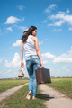 Attractive woman with old suitcase goes afar on unpaved road - PhotoDune Item for Sale