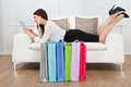 Businesswoman Using Digital Tablet With Shopping Bags On Floor - PhotoDune Item for Sale