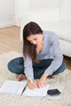 Woman Calculating Home Finances On Rug - PhotoDune Item for Sale