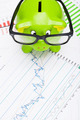 Green piggy bank over stock market chart - view from top - PhotoDune Item for Sale