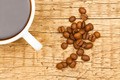 Close up of white ceramic coffee cup with roasted coffee beans on wooden table - view from top - PhotoDune Item for Sale