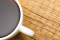 Close up of white ceramic coffee cup on wooden table - view from top - PhotoDune Item for Sale