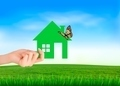 The house in hand on green natural background. - PhotoDune Item for Sale