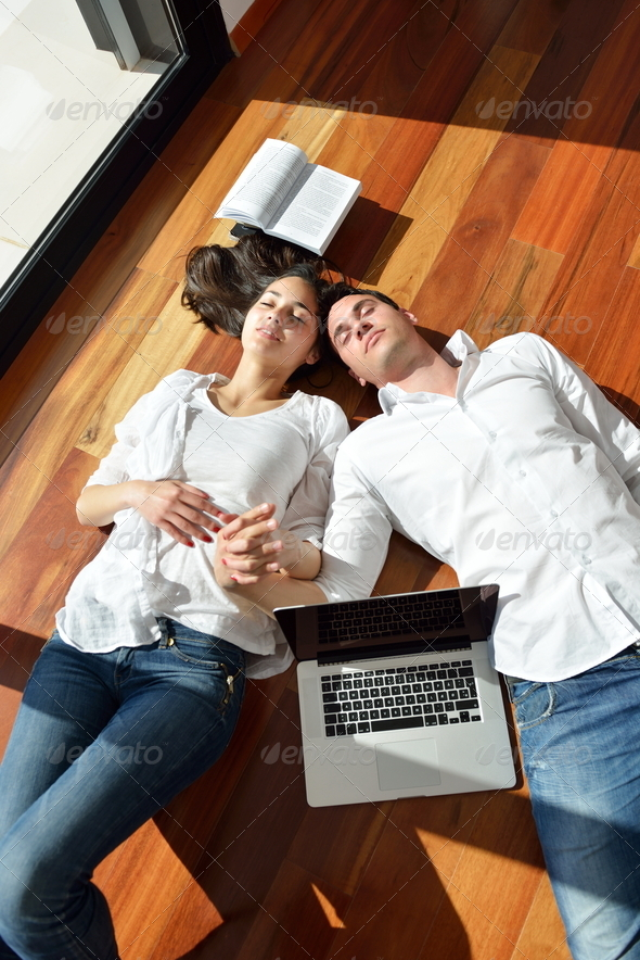 relaxed young couple working on laptop computer at home - Stock Photo - Images