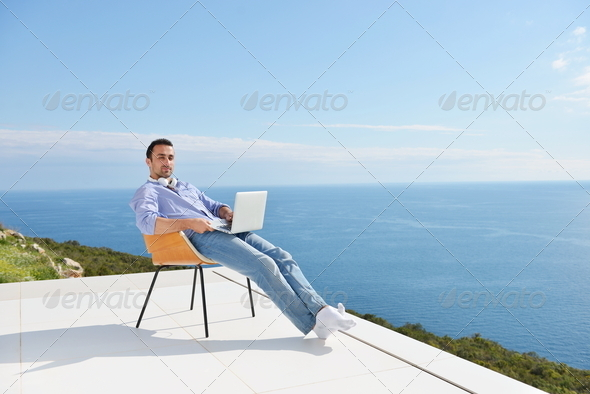 relaxed young man at home on balcony - Stock Photo - Images
