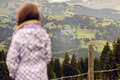 Girl standing overlooking a valley and paraglider - PhotoDune Item for Sale