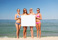 group of smiling women with blank board on beach - PhotoDune Item for Sale