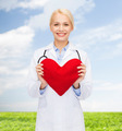smiling female doctor with heart and stethoscope - PhotoDune Item for Sale
