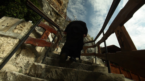 Monk Climbing Stairs To Old Church Made In Rock