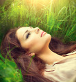 Beauty woman lying on the field and dreaming. Enjoying nature - PhotoDune Item for Sale