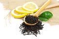 Black tea in a wooden spoon and green lemon leaves. - PhotoDune Item for Sale