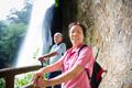 asian senior couple hiking in the mountain with waterfall background - PhotoDune Item for Sale