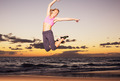 Woman jumping on the beach at sunset - PhotoDune Item for Sale