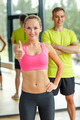 smiling man and woman showing thumbs up in gym - PhotoDune Item for Sale
