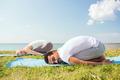 smiling couple making yoga exercises outdoors - PhotoDune Item for Sale