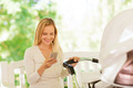 happy mother with smartphone and stroller in park - PhotoDune Item for Sale