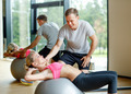 smiling young woman with personal trainer in gym - PhotoDune Item for Sale