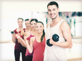 group of smiling people with dumbbells in the gym - PhotoDune Item for Sale