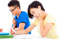 two young college students sitting an exam in a classroom  - PhotoDune Item for Sale