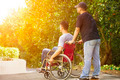 young man sitting on a wheelchair with his brother with sunlight background - PhotoDune Item for Sale