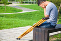 Injured Man with crutches sitting on a bench in the park - PhotoDune Item for Sale