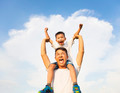 happy little boy sitting on father's shoulder with blue sky background - PhotoDune Item for Sale