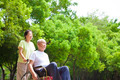 Asian senior man sitting on a wheelchair with his wife in the park - PhotoDune Item for Sale