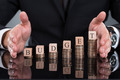 Businessman Protecting Budget Blocks On Stacked Coins - PhotoDune Item for Sale