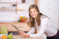 woman using digital pad in the kitchen - PhotoDune Item for Sale