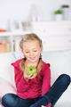 girl looking smiling at green apple - PhotoDune Item for Sale