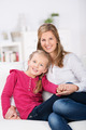 cute little girl sitting on sofa with her mother - PhotoDune Item for Sale