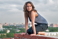 Young beautiful woman sitting on residental building roof - PhotoDune Item for Sale