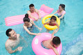 Family and friends playing in the water at the pool with inflatable tubes