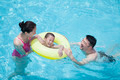 Smiling happy family playing in the pool with their son in an inflatable tube