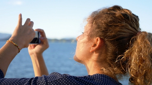 Girl Taking Photo of Island by Smart Phone